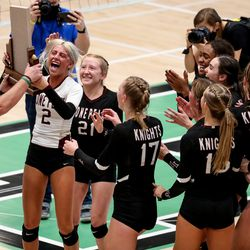 Lone Peak's Grace Evans receives the trophy as her team celebrates its win over Copper Hills in the 6A volleyball championship match at Hillcrest High School in Midvale on Saturday, Nov. 7, 2020.
