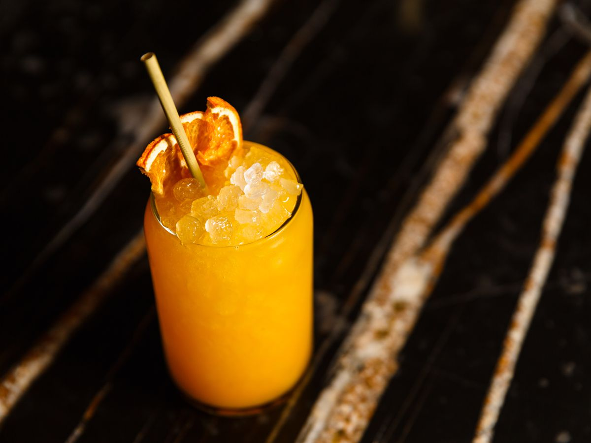 An orange cocktail garnished with orangle slices and a paper straw set on a dark table with decorative light brown streaks.