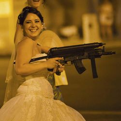 In this Sunday, Aug. 26, 2012 photo shot under iodine street lighting, a Romanian bride holds toy weapons at the Triumph Arch in Bucharest, Romania. The arch, a replica of the Arc de Triomphe in Paris, the French capital, is a rendezvous place for brides on the wedding night for the bride stealing ritual. The ancient Romanian tradition of bride stealing is getting bigger, brasher and an increasingly common sight in the Romanian capital, the region's undisputed party town.