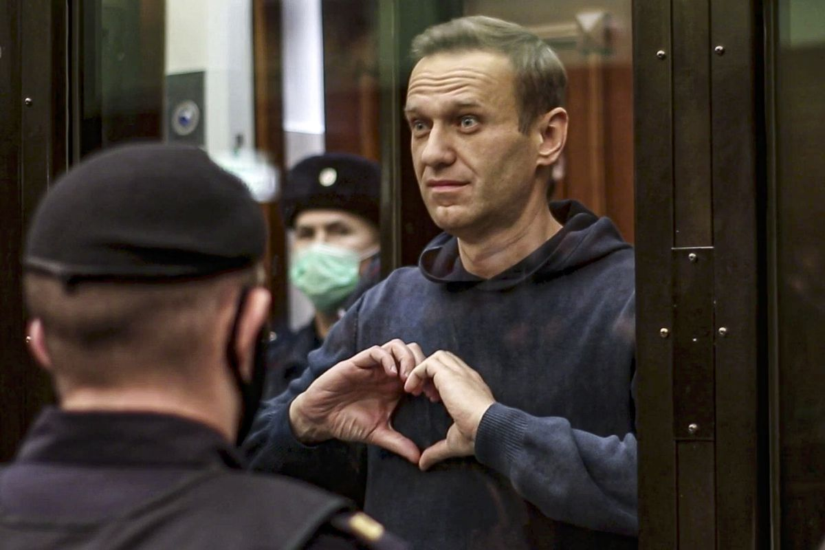 In this handout photo taken from a footage provided by Moscow City Court on Tuesday, Feb. 2, 2021, Russian opposition leader Alexei Navalny shows a heard symbol standing in the cage during a hearing to a motion from the Russian prison service to convert the suspended sentence of Navalny from the 2014 criminal conviction into a real prison term in the Moscow City Court in Moscow, Russia.