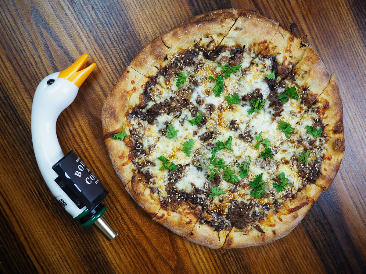 A pizza on a wooden table with a Goose Island beer handle.