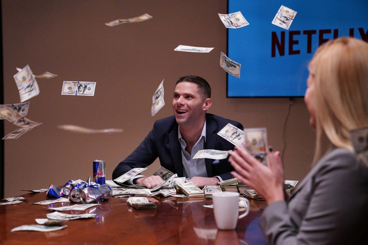 An actor at a Netflix conference table is showered with cash while a woman sits by and applauds.