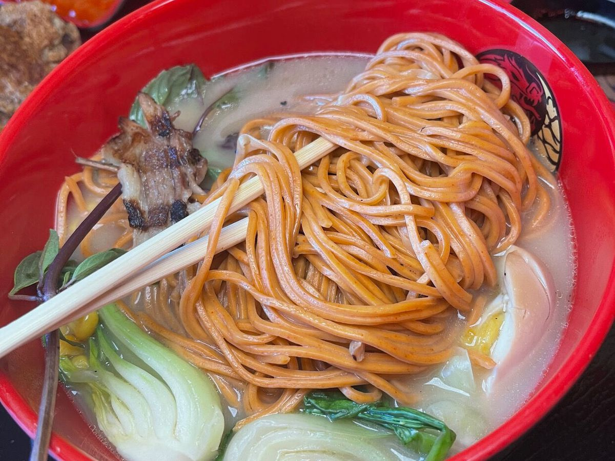 A red bowl with ramen, broth, and vegetables