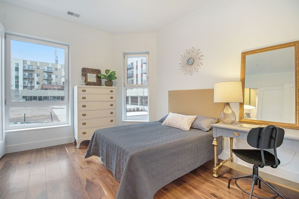A bedroom with a twin bed and gray sheets. A bedside table, mirror, and rolling chair are next to the bed. There's two windows looking out an another apartment building.