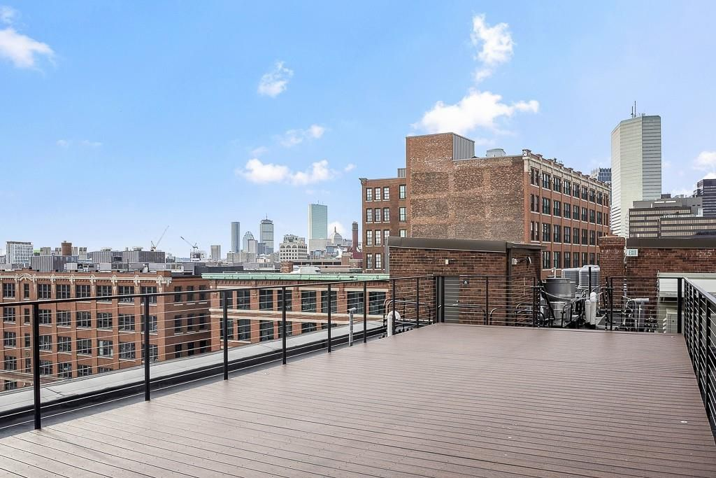 A long, somewhat narrow roof deck with views of skyscrapers in a city's downtown area.