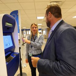 Maddie Frommelt, CLEAR ambassador, talks with Ricky Gambill, CLEAR Salt Lake City supervisor, during the launch of a new biometric, fee-based service that allows travelers to move past manual ID verification lines using fingerprints and iris scans, at the Salt Lake City International Airport in Salt Lake City on Wednesday, July 12, 2017.