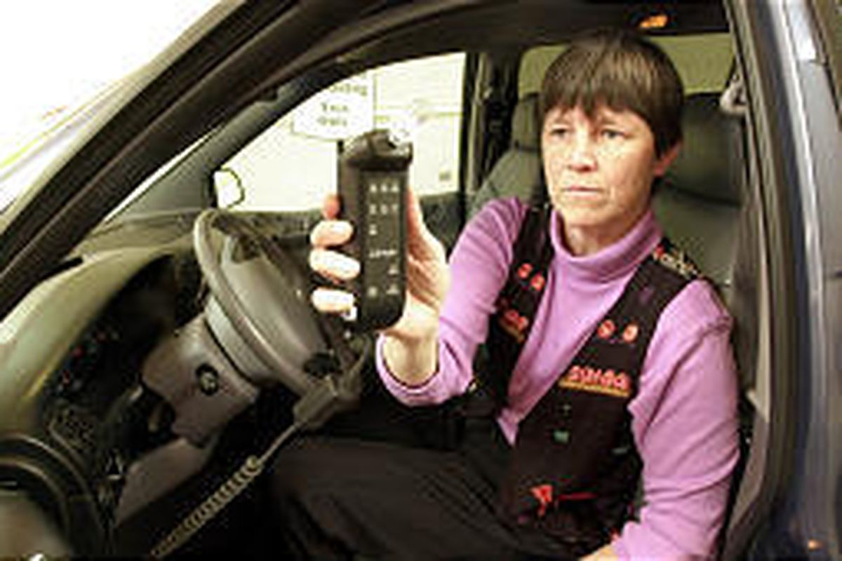Mary Philips holds a device that can detect alcohol on a driver's breath and won't allow the car to start if it gets a positive reading.