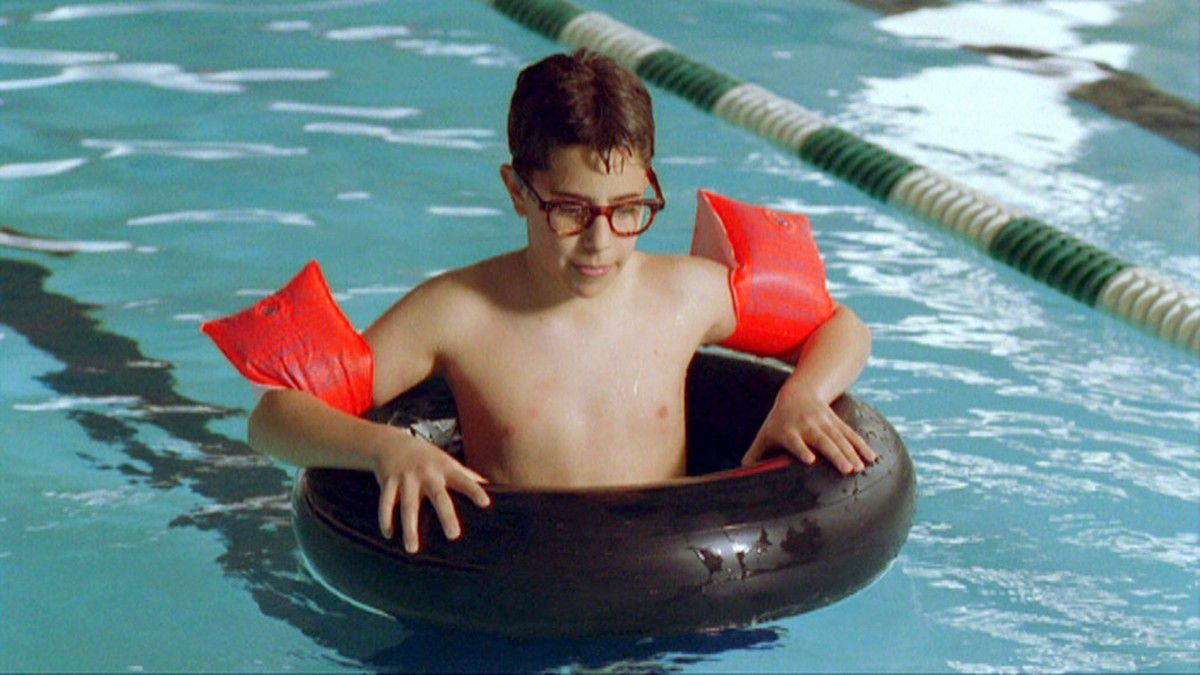 the kid from the thirteenth year in an inner tube wearing water wings