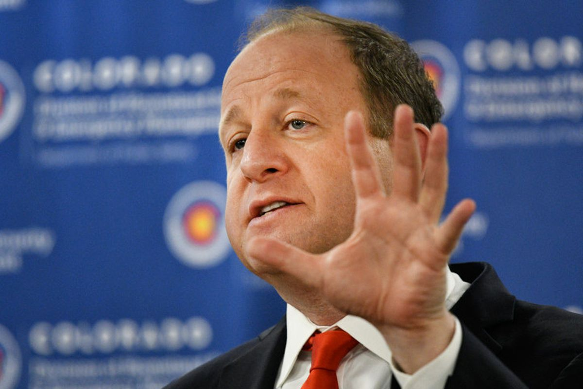 Governor Jared Polis gestures with his hand while speaking.