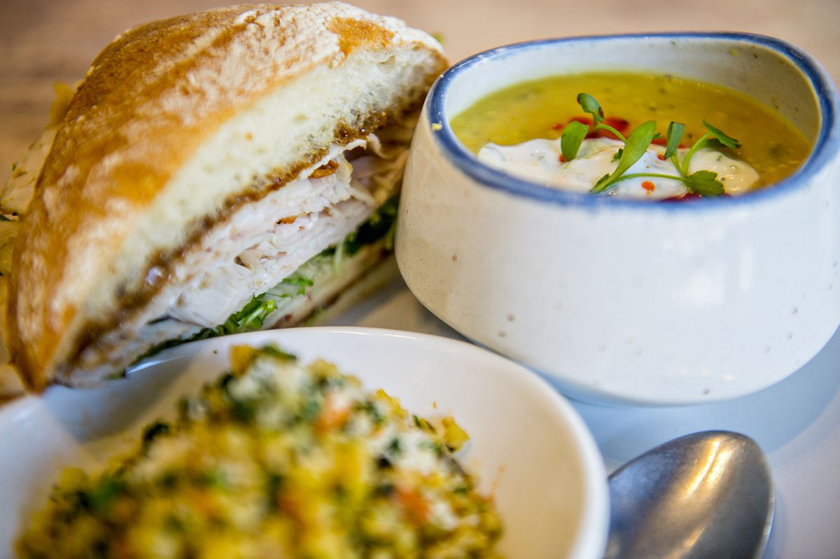 The warm house roasted turkey sandwich with mustard, pickles, and Swiss with a side of curried lentil soup at Ivy on 7th