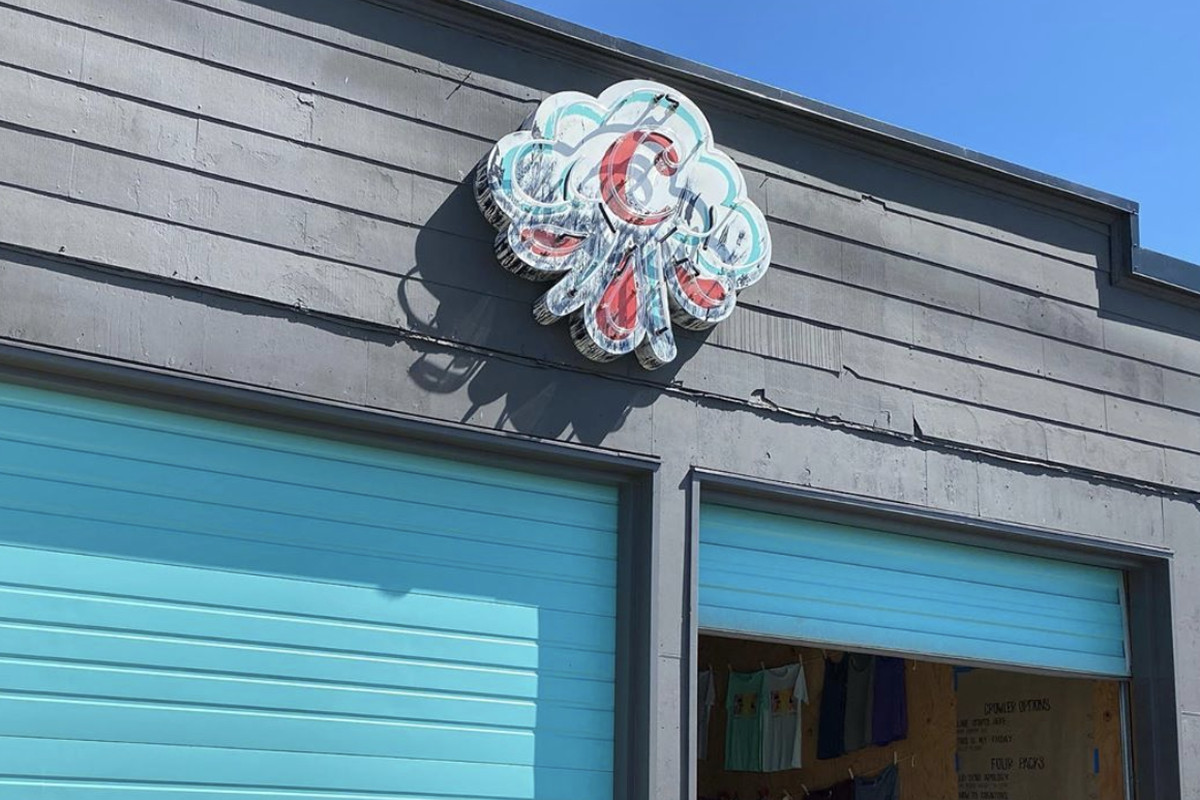 The Cloudburst Brewing logo on top of its new Ballard taproom, with a light-blue painted garage door below