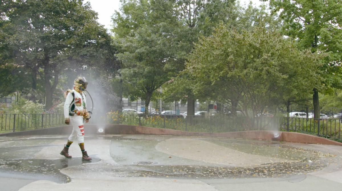 a person in a strange white bodysuit and helmet walks through sprinklers in an urban park in The Hottest August