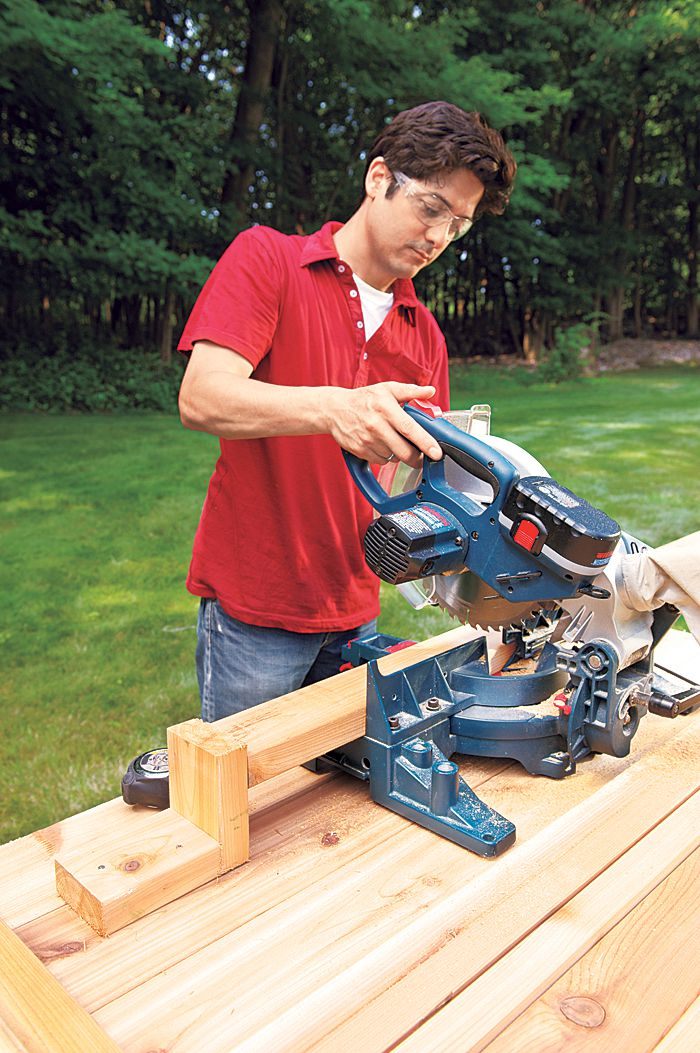 Man Cuts Wood Planks For Planter Bench With Miter Saw