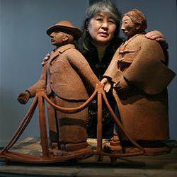 "Artist Etsuko Ogura displays her sculpture ""Immigrants"" of her grandparents at the Art Access Gallery."
