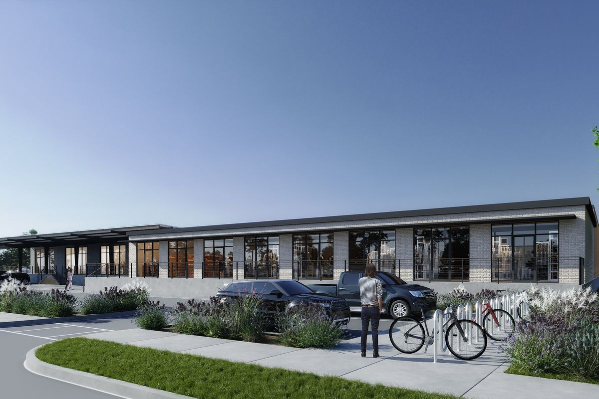A rendering of the Docs shows a parking lot and a one-story white building with blue skies in the background and bike racks in the foreground.