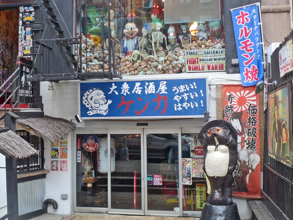 A jumbled pair of storefronts with a life size strange creature in front, and all sorts of skeleton themed art above this classic Japanese restaurant.
