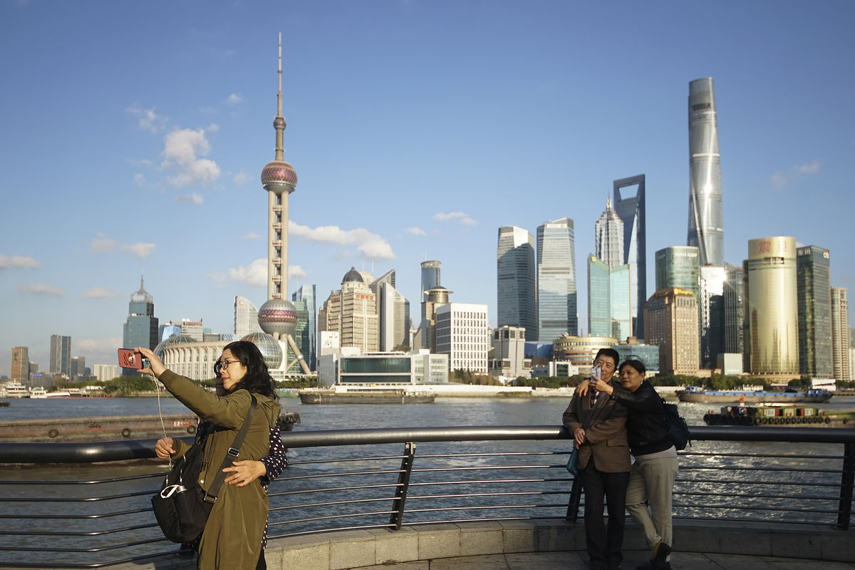 People take selfies of the Pudong skyline as they stand on the Bund in Shanghai, China.