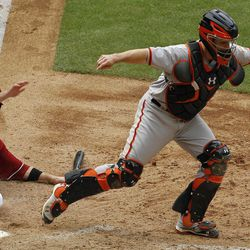 San Francisco Giants' Buster Posey (28) takes a throw wide of home plate as Arizona Diamondbacks' Aaron Hill slides in to score during the seventh inning in an MLB baseball game Sunday, April 8, 2012, in Phoenix.