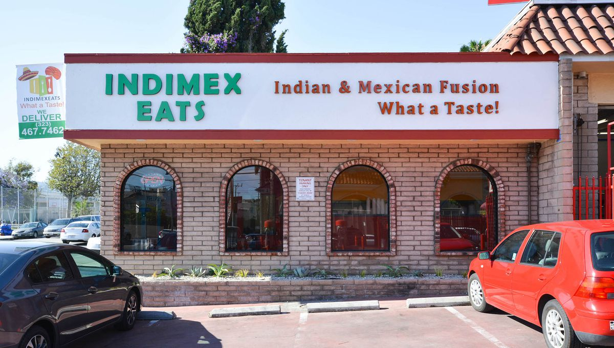 A bright, brick restaurant showcases Mexican and Indian flavors from the outside.