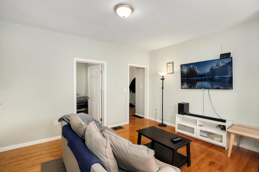Another angle on the living room, with two windows leading out of it and a TV mounted on the wall.