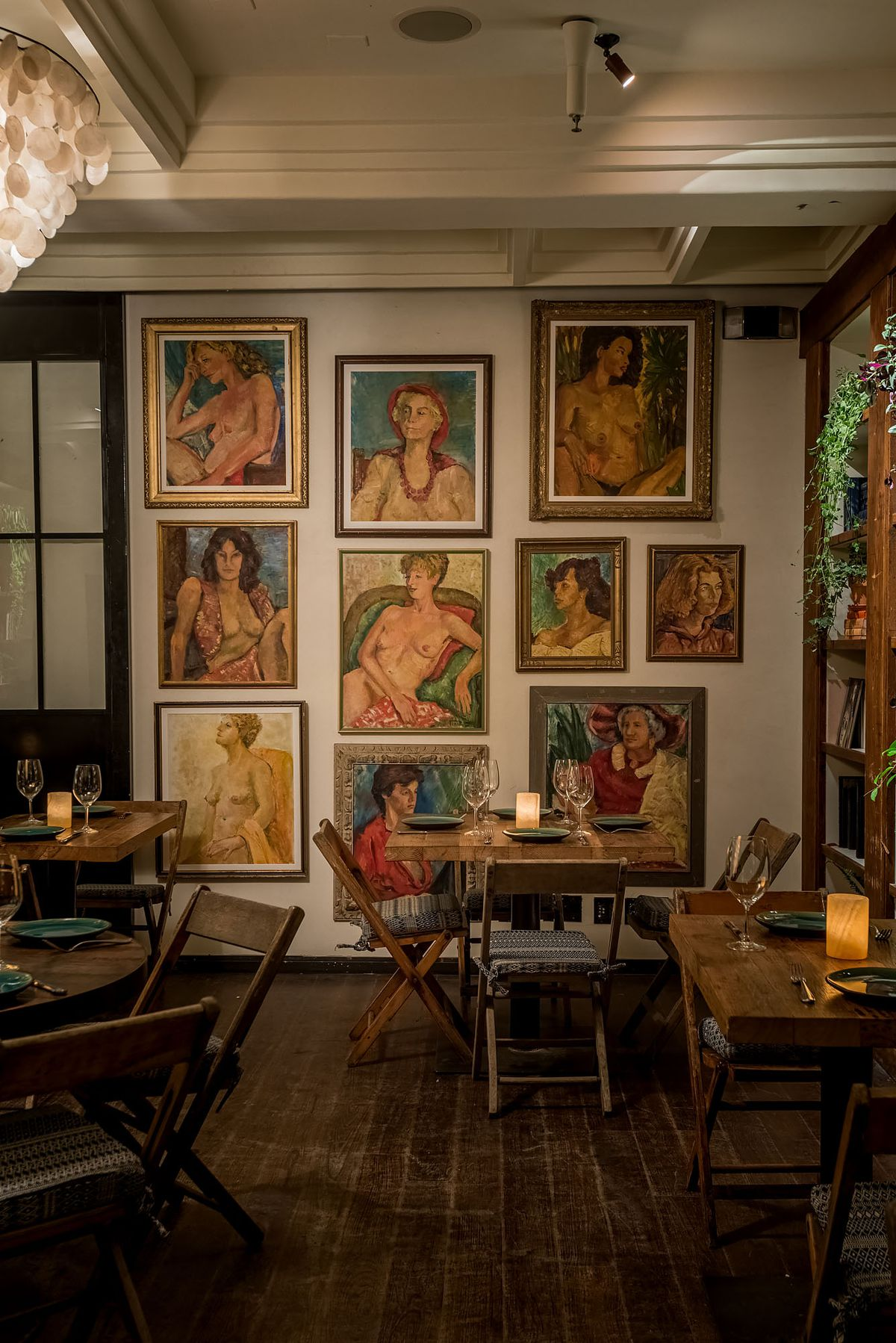 Painted artwork depicting women at various ages hangs on a restaurant wall.