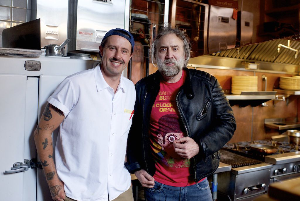 A photograph of Gabriel Rucker and Nicolas Cage standing side by side in a restaurant kitchen