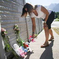 Rachele Morgan leaves a stuffed animal at a small memorial to the victims of Tuesday's fatal shooting on Alta Canyon Drive in Sandy on Wednesday, June 7, 2017.