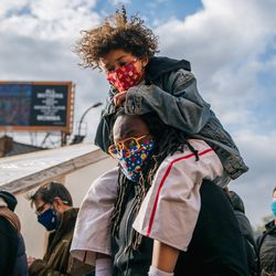 A child sits on his father's shoulders at a gathering at the intersection of 38th Street and Chicago Avenue following the verdict in the Derek Chauvin trial on April 20, 2021 in Minneapolis, Minnesota