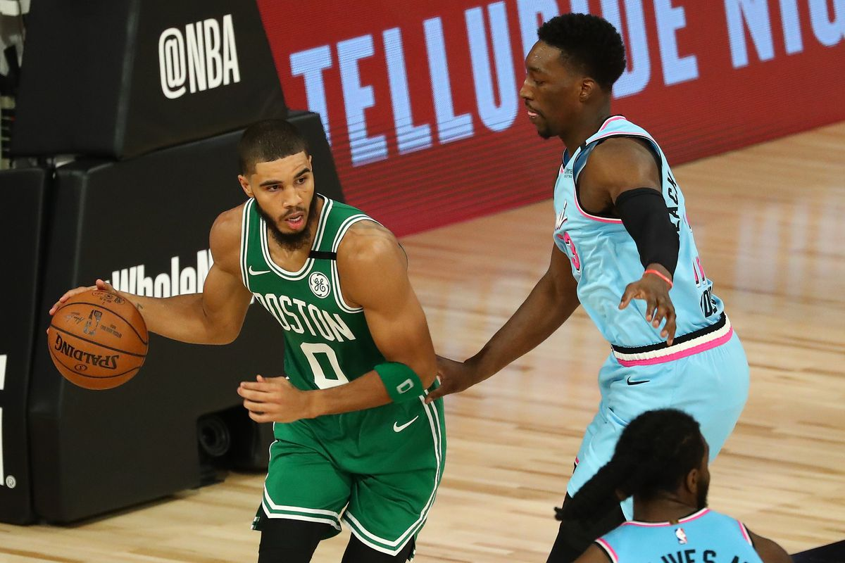 Jayson Tatum of the Boston Celtics controls the ball against Bam Adebayo of the Miami Heat in the second half of an NBA game at HP Field House at ESPN Wide World Of Sports Complex on August 4, 2020 in Lake Buena Vista, Florida.
