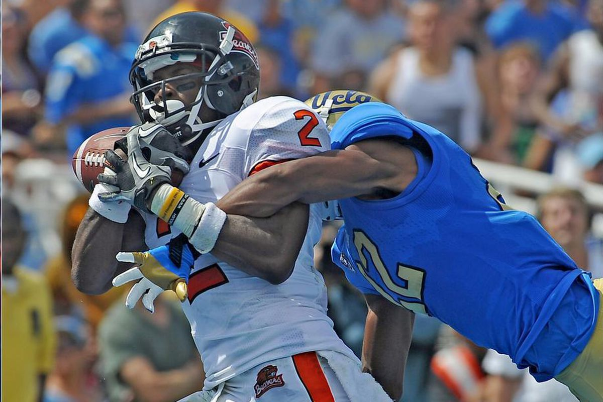 Markus Wheaton pulls in a touchdown pass despite the efforts of UCLA's  Sheldon Price. <em>(US Presswire photo by Jamie Kamin-Oncea)</em>