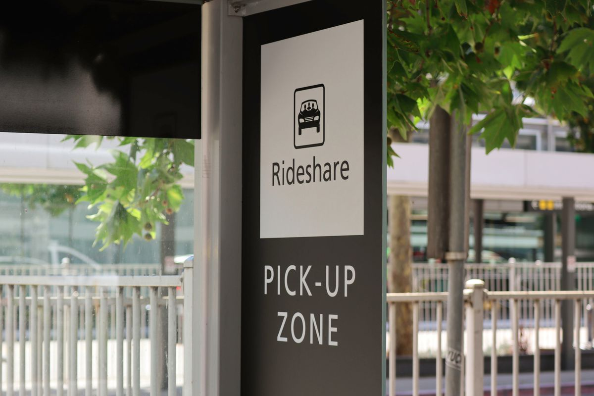 A vertical rectangular sign hanging on a post. It has a graphic drawing of a car and says Rideshare in a square border. Under that square, it says Pick-Up Zone. Foliage and railings are in the background.