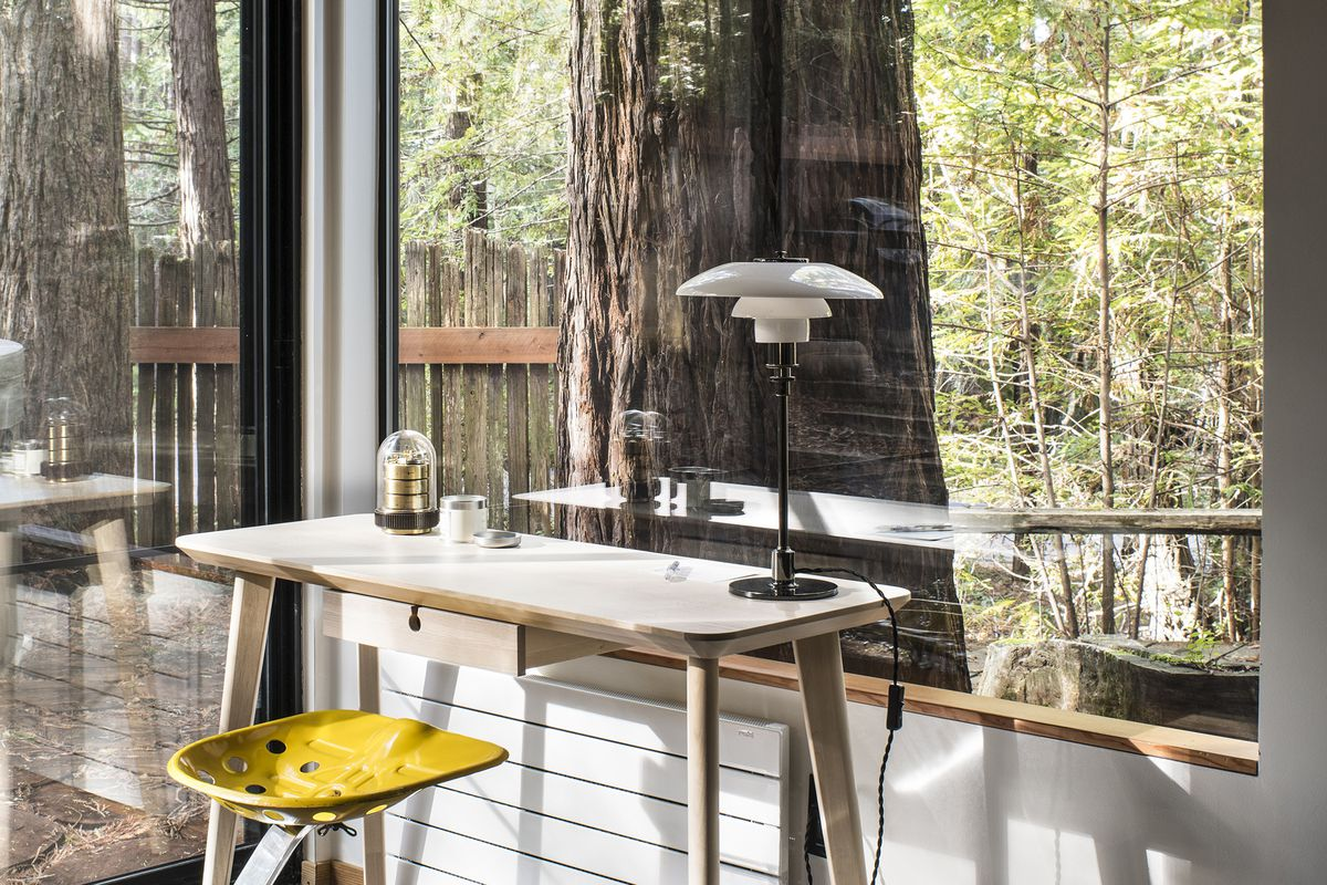 A white desk with a yellow metal stool in front of a large window with views to a redwood forest