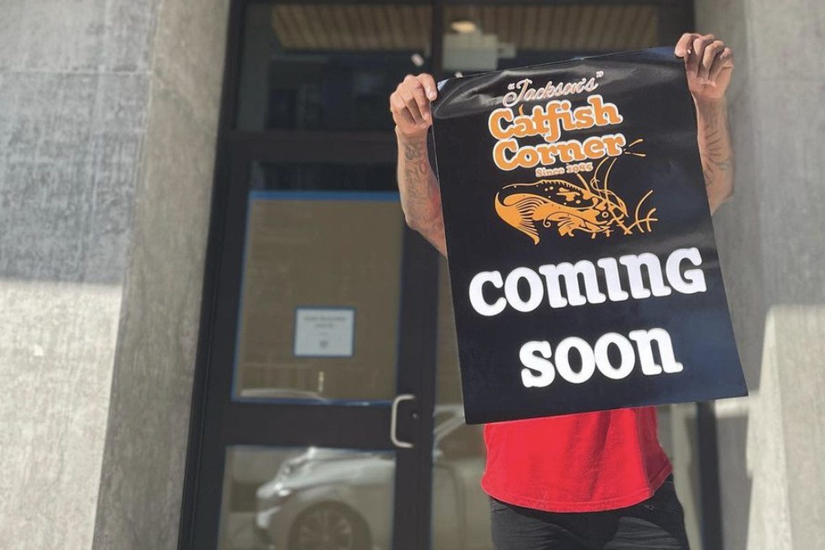 """Jackson's Catfish Corner owner Terrell Jackson holds up a sign with the restaurant's logo and the words """"Coming Soon"""""""