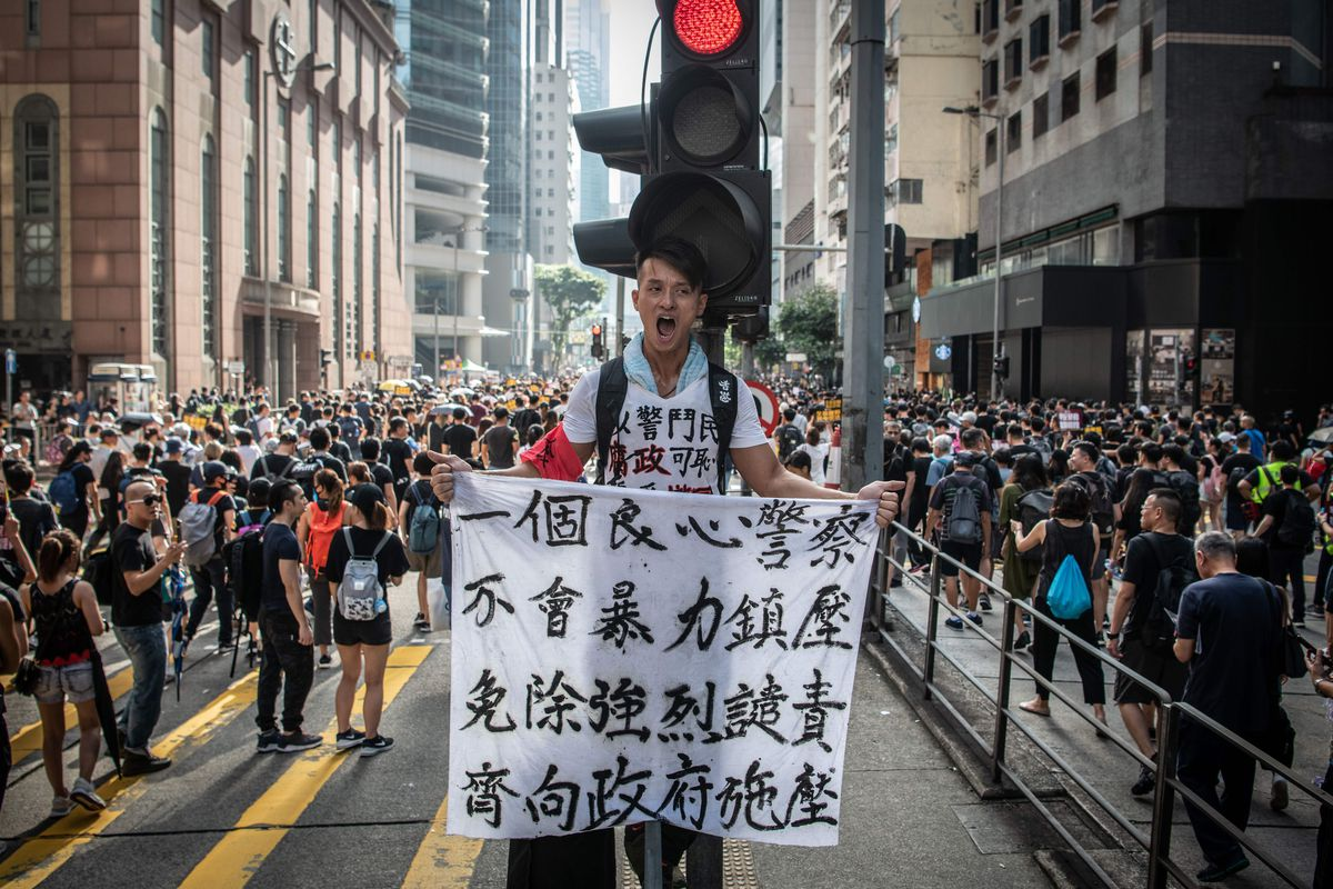 A Hong Kong man holds a sign amid a large group of protesters on a Wan Chai, Hong Kong street.