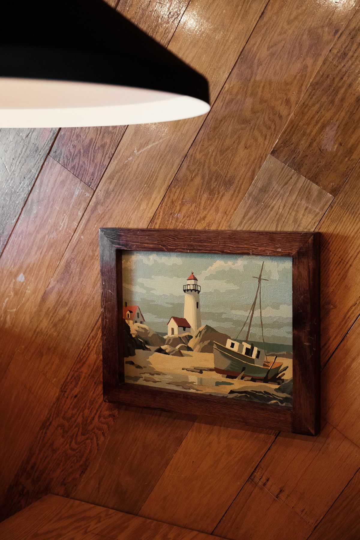 A painting of ships and a lighthouse in a wood frame against wood paneling in a booth at Michigan & Trumbull.