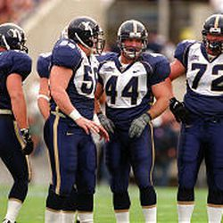 """BYU defensive players Jeff Holtry (45), Chris Hoke (55), Rob Morris (44) and Hans Olsen (72) show off their uniforms during a game against Washington in 1999. The """"bib"""" style uniform lasted just one season."""