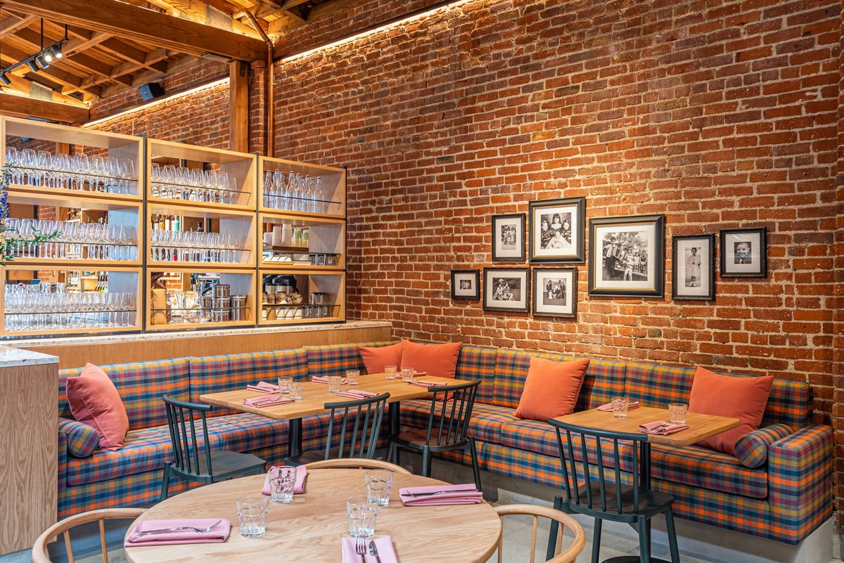 A wide corner booth with plaid seating inside of a new restaurant with brick walls.