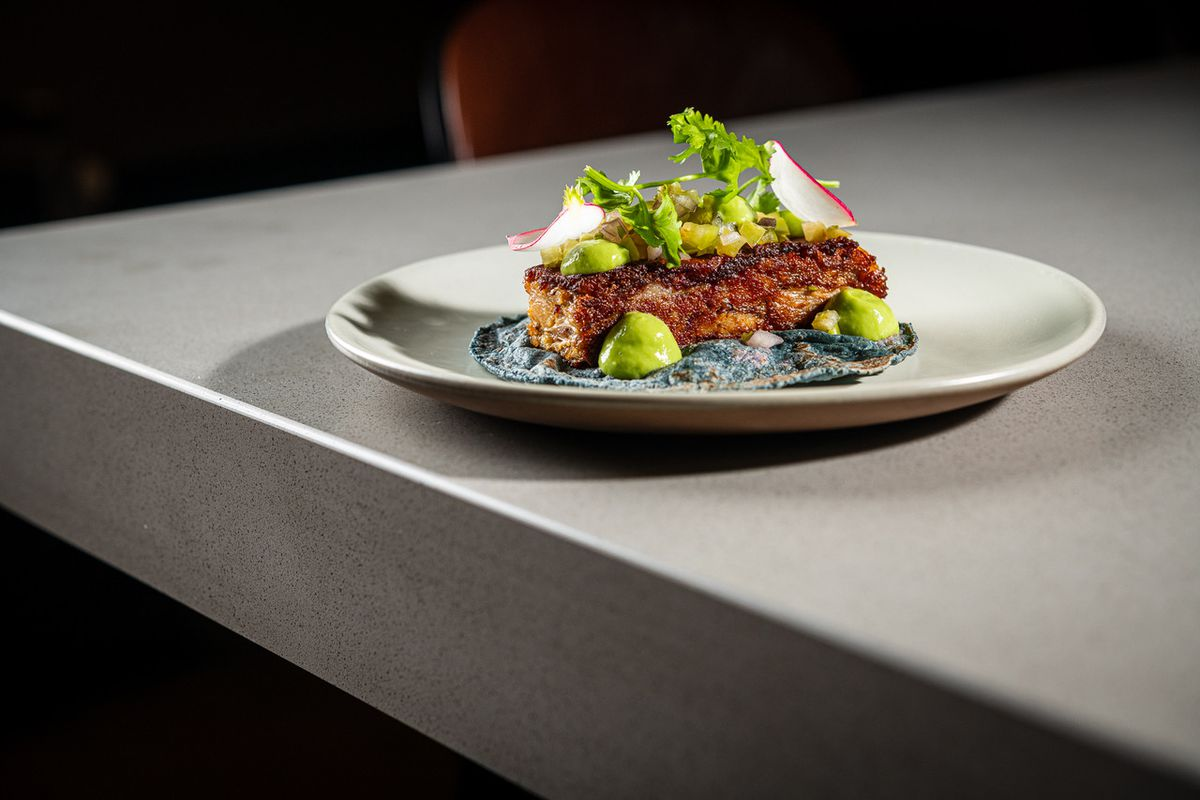A rectangular slice of suckling pig terrine sits on top of a blue corn tortilla studded with dots of lime-green avocado puree and tomatillo salsa at Maiz64.