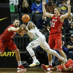 Oregon forward Mikyle McIntosh (22) steps over a fallen Utah player as Utah forwards David Collette, left, and Tyler Rawson defend during an NCAA college basketball game Friday, Dec. 29, 2017, in Eugene, Ore. Utah won 66-56. (AP Photo/Thomas Boyd)
