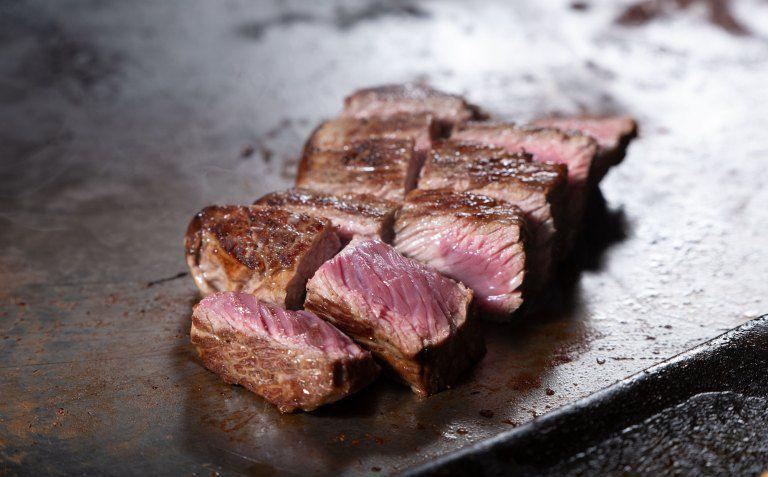 Sliced steak cooking on a griddle.