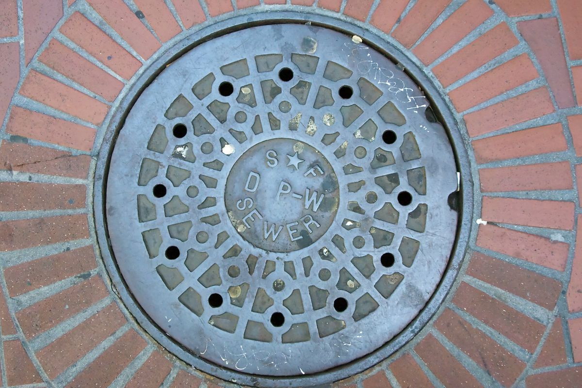 """A manhole over on a brick street, which reads, """"SF SEWER."""""""
