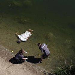 Michelle Harward, left, and Andy Pacejka look over a mock crime scene in Murray as a mannequin floats in the water next to them.