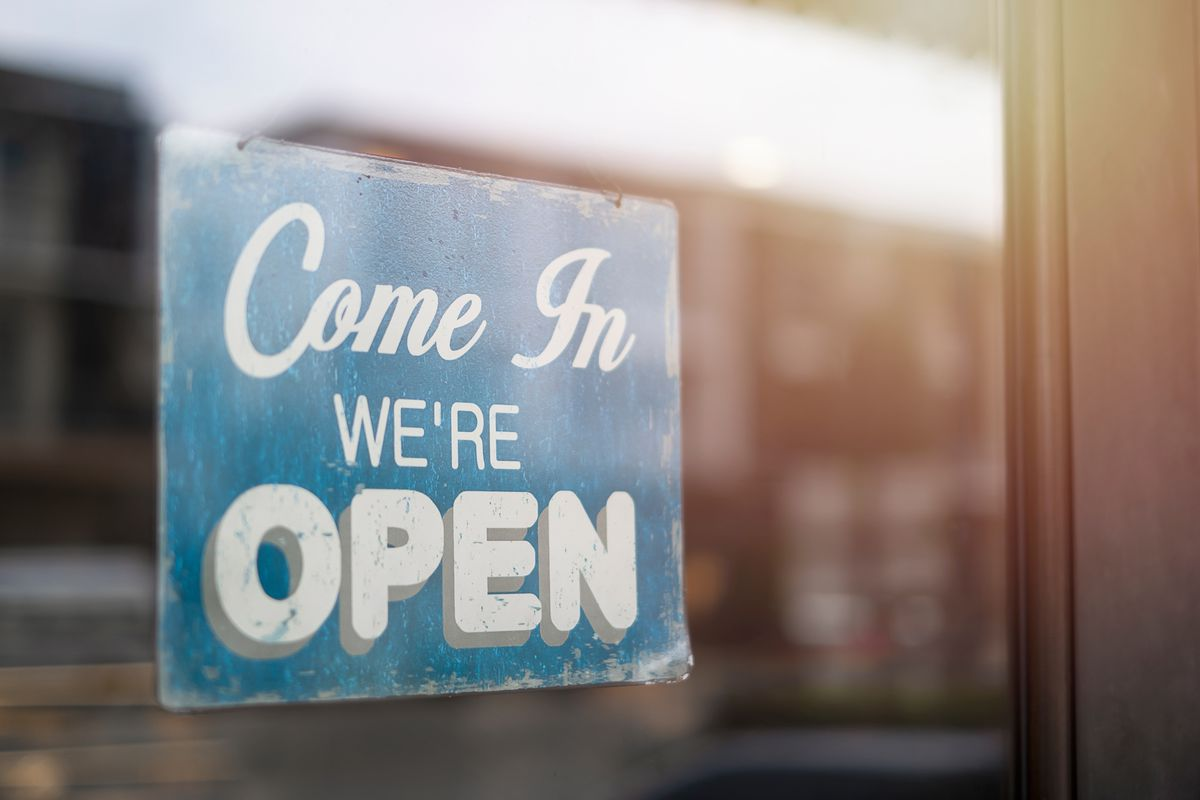 """A """"Come in, we're open"""" sign on a window of a restaurant"""