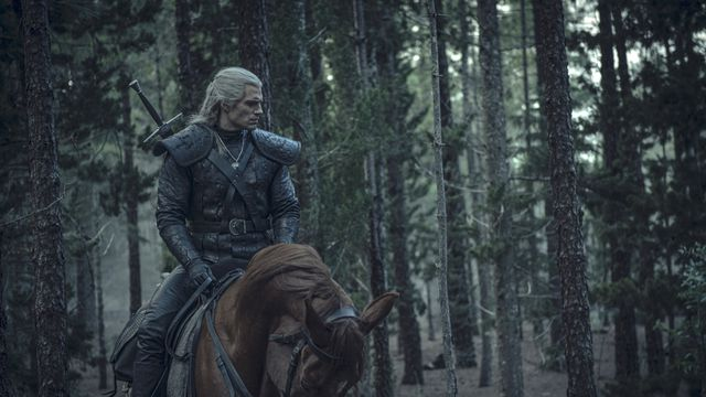 geralt rides roach the horse in the woods in the witcher on Netflix