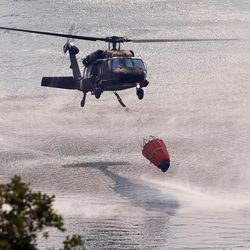A Blackhawk helicopter dips water as  a fire burns near Weber Canyon on Tuesday, Sept. 5, 2017.