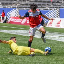Johan Gomez (9) jumping over a slide tackle during the opening match of the 40th Annual Dallas Cup.