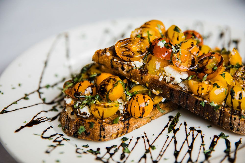 Two slices of toast are topped with halved cherry tomatoes, goat cheese, a balsamic drizzle, and more