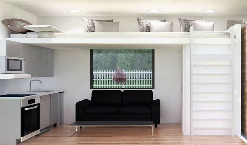 The interior of a shipping container with a lofted bed, a couch, a bathroom, a kitchen area.