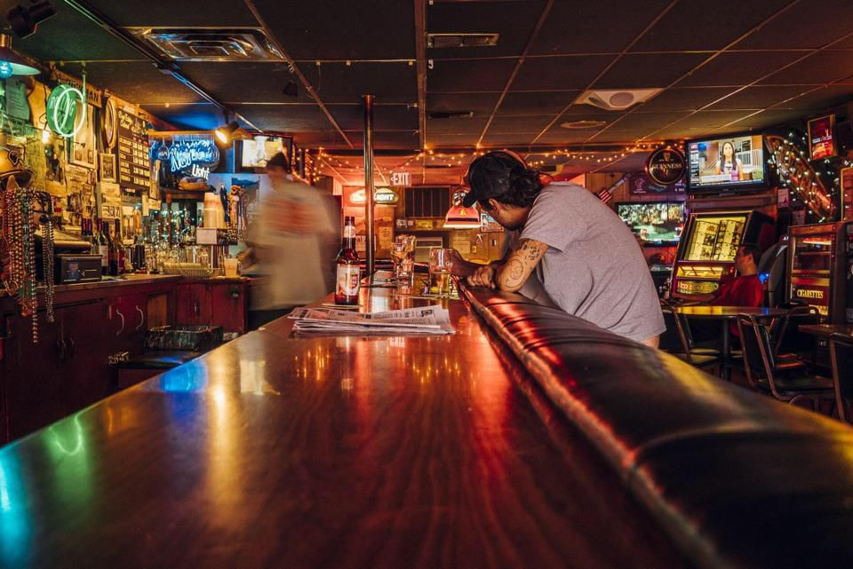 A person sits at a wooden bar with liquor shelves on the other side.