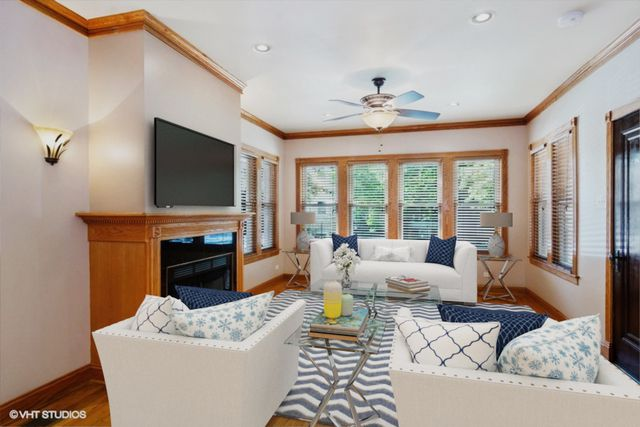 A living room with a wood fireplace mantle and a row of windows at the far end. There are virtually staged couches and a coffee table.